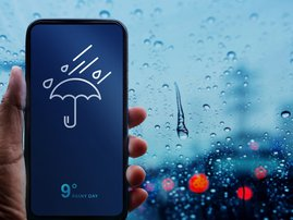 Rainy Day Concept. Hand Holding Smartphone with Weather Information show on Screen.