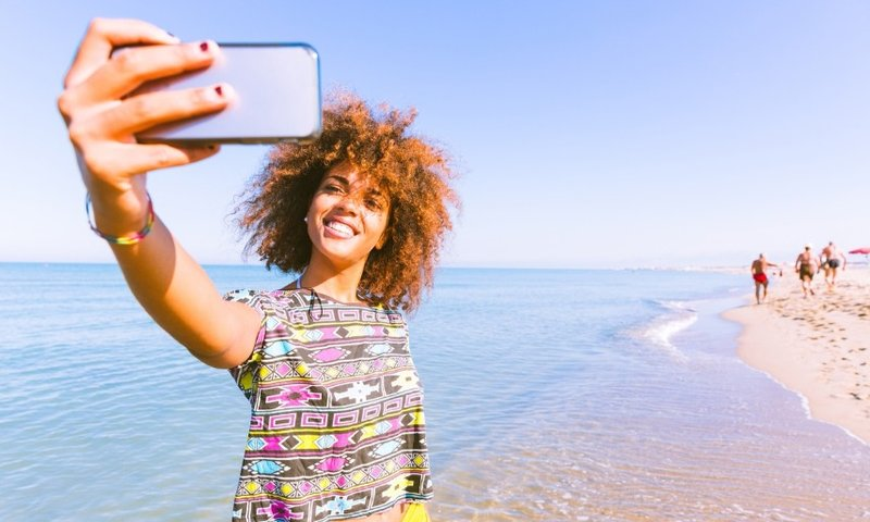 Woman travel phone selfie beach