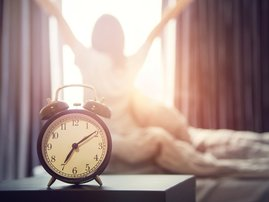 Woman waking up alarm clock morning