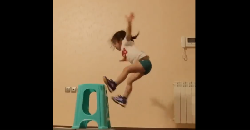 little girl jumping of a stool