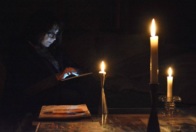 Woman reading book with candles
