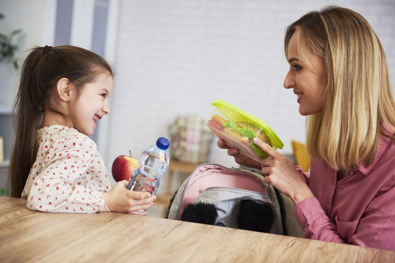 Mom putting lunch box with healthy food in backpack