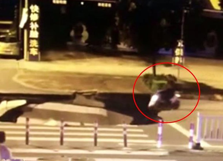 Motorcyclist rides into sinkhole while talking on handphone