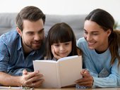 Parents reading a book with daughter