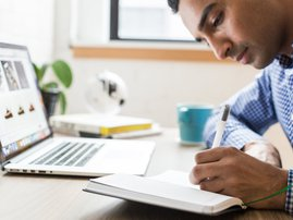 man writing with his left hand
