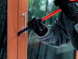 Burglar with crowbar trying to break a door