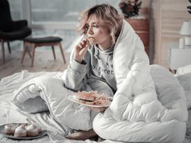 Sad woman eating junk food