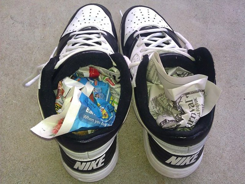 Ilustrasi gulungan koran dalam sepatu