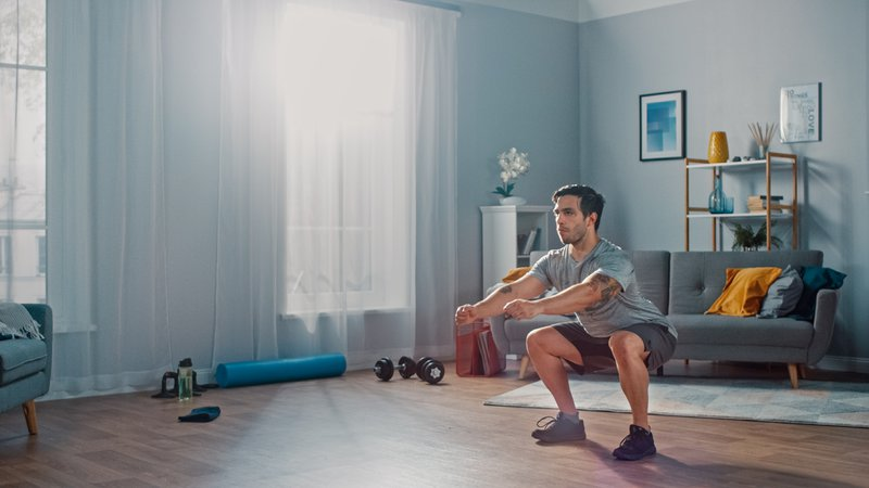 Man in T-shirt and Shorts Doing Squat Exercises at Home