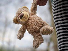 stuffed teddy bear held by a girl child