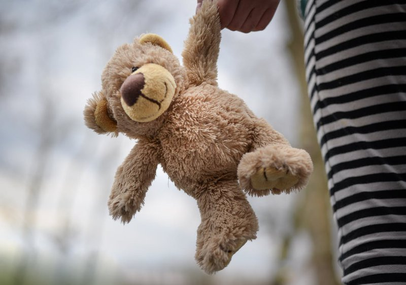 stuffed teddy bear held by a girl child