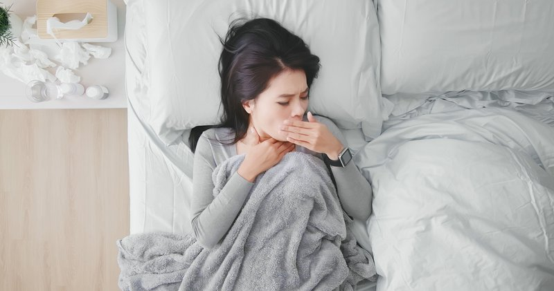Woman coughing in bed