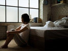 Woman sitting alone in bedroom