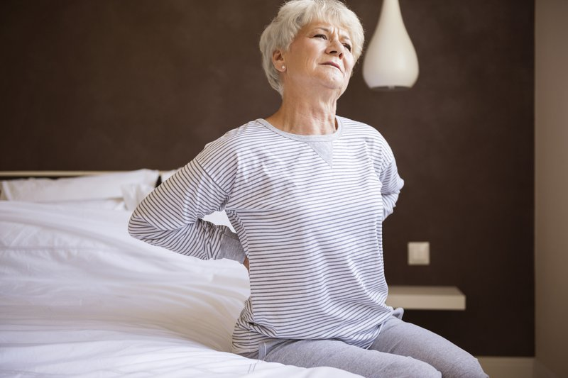 Woman sitting on an uncomfortable bed